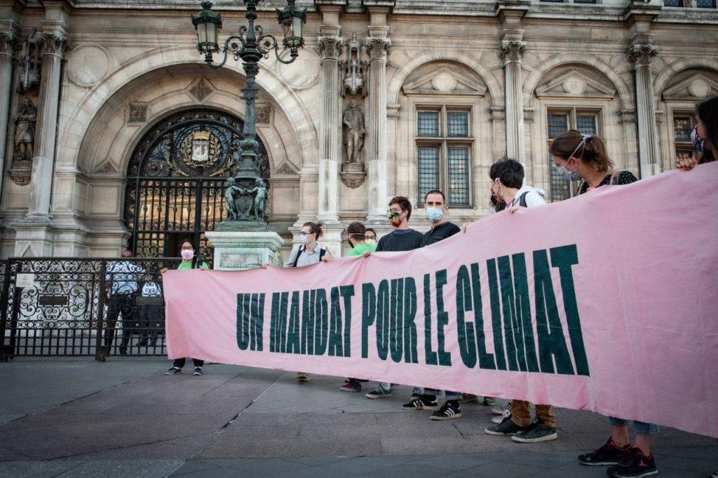"""Des militants écologistes non-violents comparaissent pour avoir décroché les portraits du président de la République dans les mairies. Personnage portant un masque à gaz dans une ville démoli, devant un portrait d'Emmanuelle Macron accroché sur un bout de mur : """"Y'a pas à dire ! A l'époque... On savait hiérarchiser les problèmes !"""""""